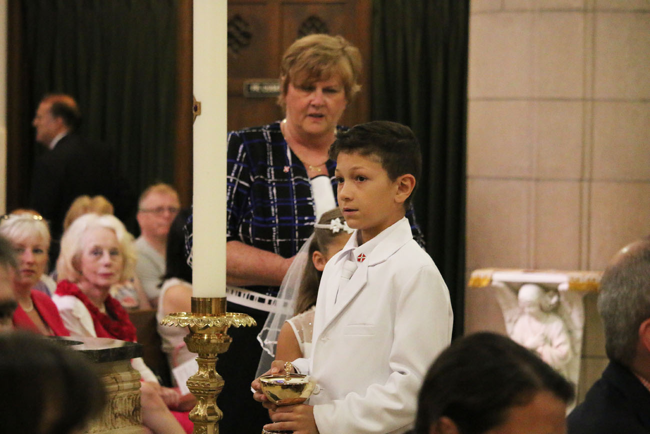 Children help bring up the offertory gifts during the centennial Mass.