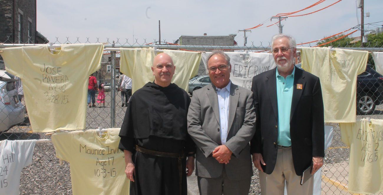 Standing at St. Rita's Shrine in Philadelphia in front of a line of T-shirts representing young men who have died from gun violence this year in the city are, from left, Augustinian Father Joseph A. Genito, shrine director; James Amato, secretary for archdiocesan Catholic Human Services; and Bryan Miller, founder of the group Heeding God's Call to End Gun Violence, which helped organize a community event at the shrine May 25. (Photo by Lou Baldwin)