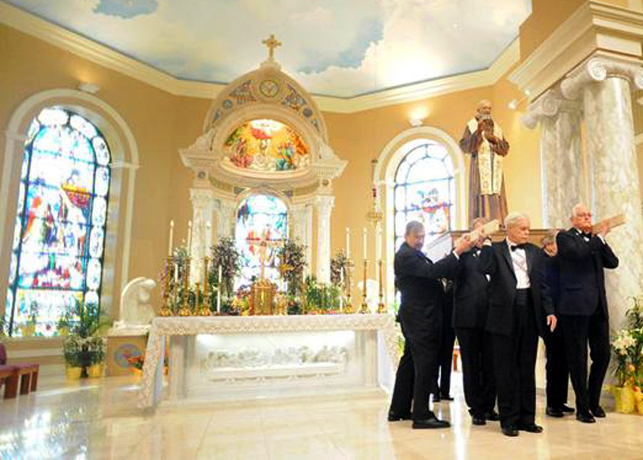 Men of St. Bede Parish, Holland, carry a statue of St. Pio of Pietrelcina in the church.