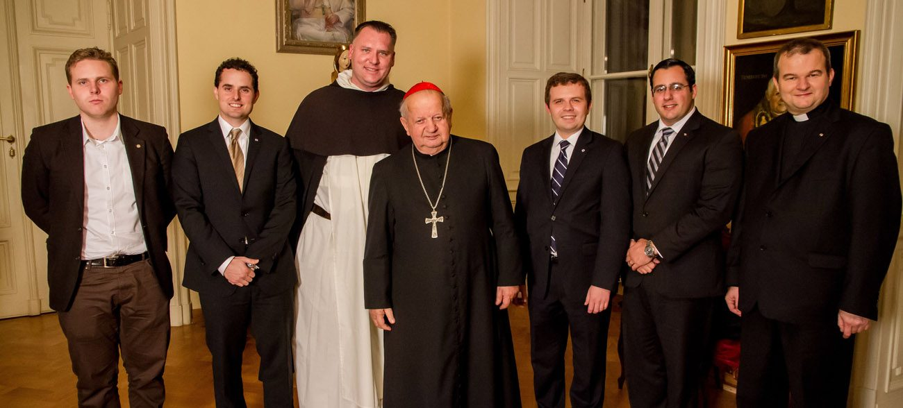 "Polish Cardinal Stanislaw Dziwisz, former personal secretary to St. John Paul II, center, poses at his residence in Krakow with special guests and members of the production team for ""Liberating a Continent: John Paul II and the Fall of Communism."" The documentary will be broadcast on PBS stations throughout the month of June. (CNS photo/George Hosek, Liberating a Continent)"