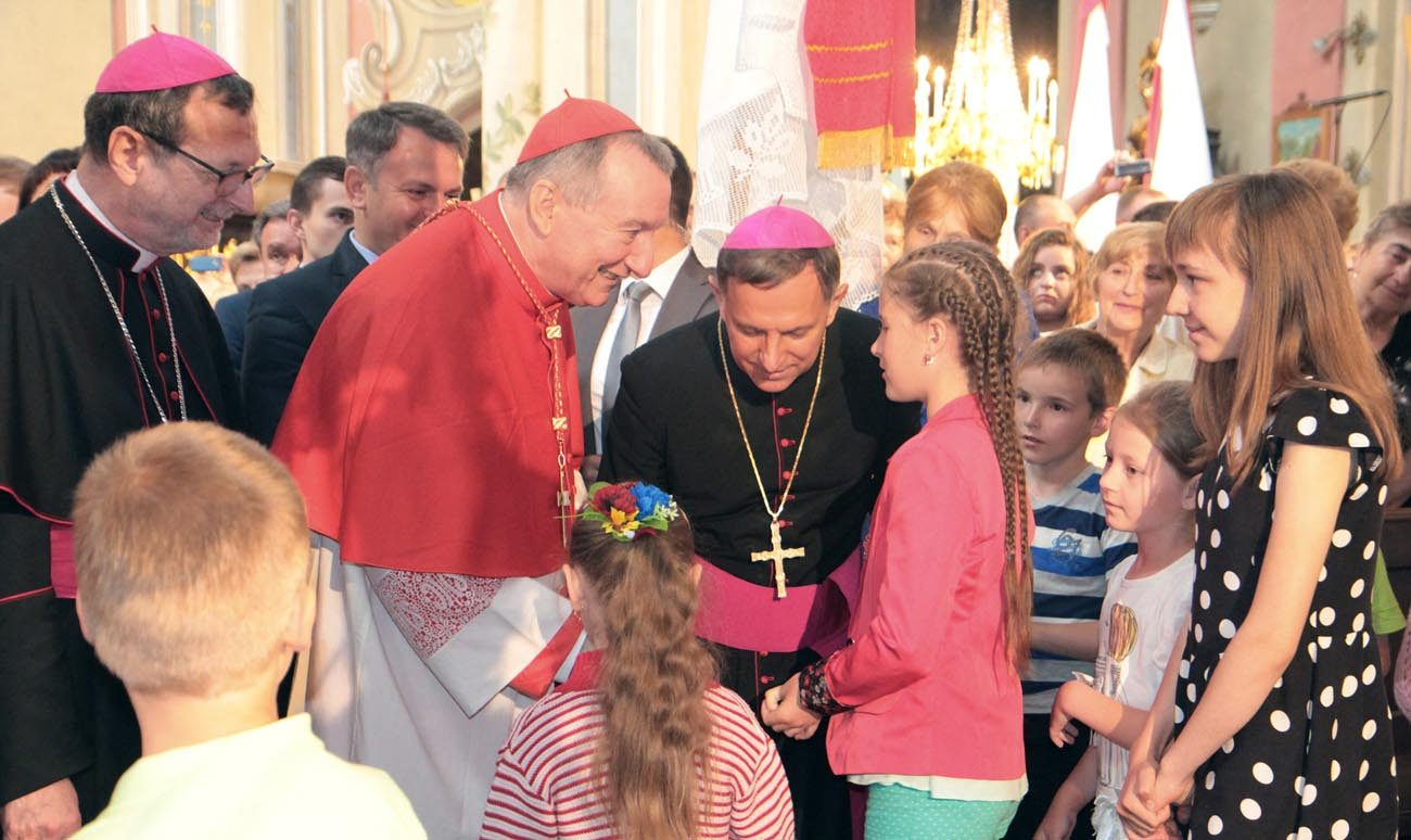 Cardinal Pietro Parolin, Vatican secretary of state, in red vestments, greets young people during a June 18 visit to Lviv, Ukraine. Although his visit included meetings with the state officials, church leaders and religious communities, Cardinal Parolin said the main purpose was to express the solidarity with people suffering from the war in the east. (CNS photo/courtesy Olena Kulygina)