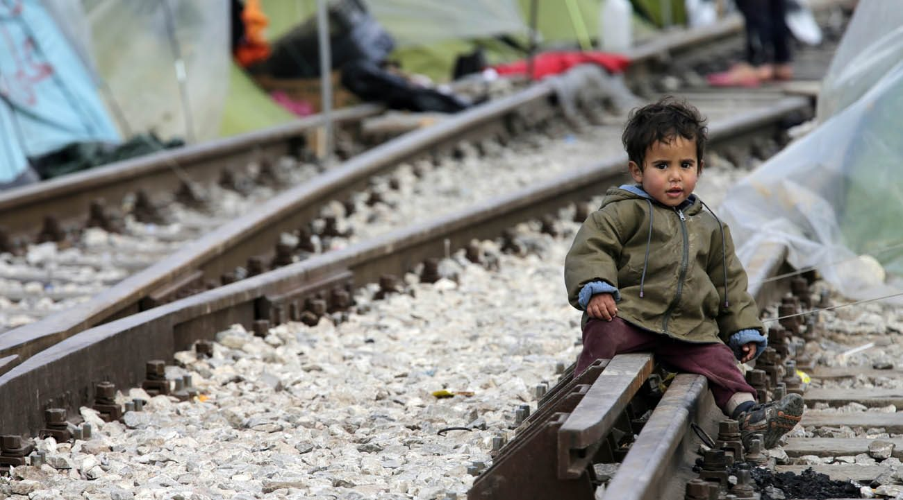 A child sits on railroad tracks near a makeshift camp for migrants in late March at the Greek-Macedonian border near the village of in Idomeni, Greece. Migrant children, the most vulnerable and fragile victims of war and persecution, will be at the heart of the Catholic Church's annual day of reflection and prayer on the situation of migrants and refugees. (CNS photo/Armando Babani, EPA)