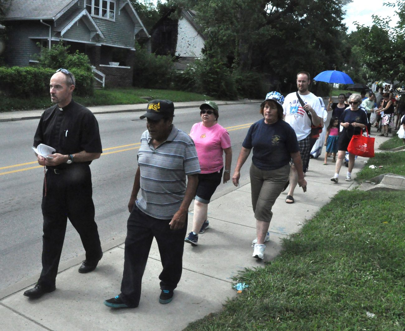 Father Christopher Wadelton, pastor of St. Philip Neri Parish in Indianapolis, leads a group in praying the rosary July 10 while walking through the church's neighborhood. The parish is sponsoring a series of nine consecutive prayer walks in response to increased drug problems and violent crimes in its neighborhood. (CNS photo/Sean Gallagher, The Criterion)
