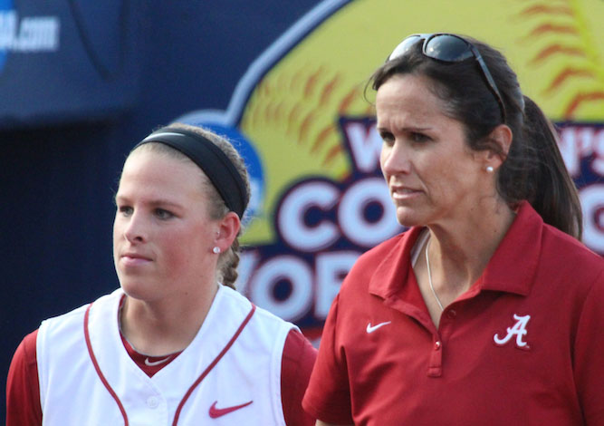 Alabama women's softball assistant head coach Alyson Habetz, right, is pictured with a player during a 2014 game in Oklahoma City. Since the Catholic coach arrived in 1998, Alabama has made nine trips to the World Series. (CNS photo/Fastpitch.TV)