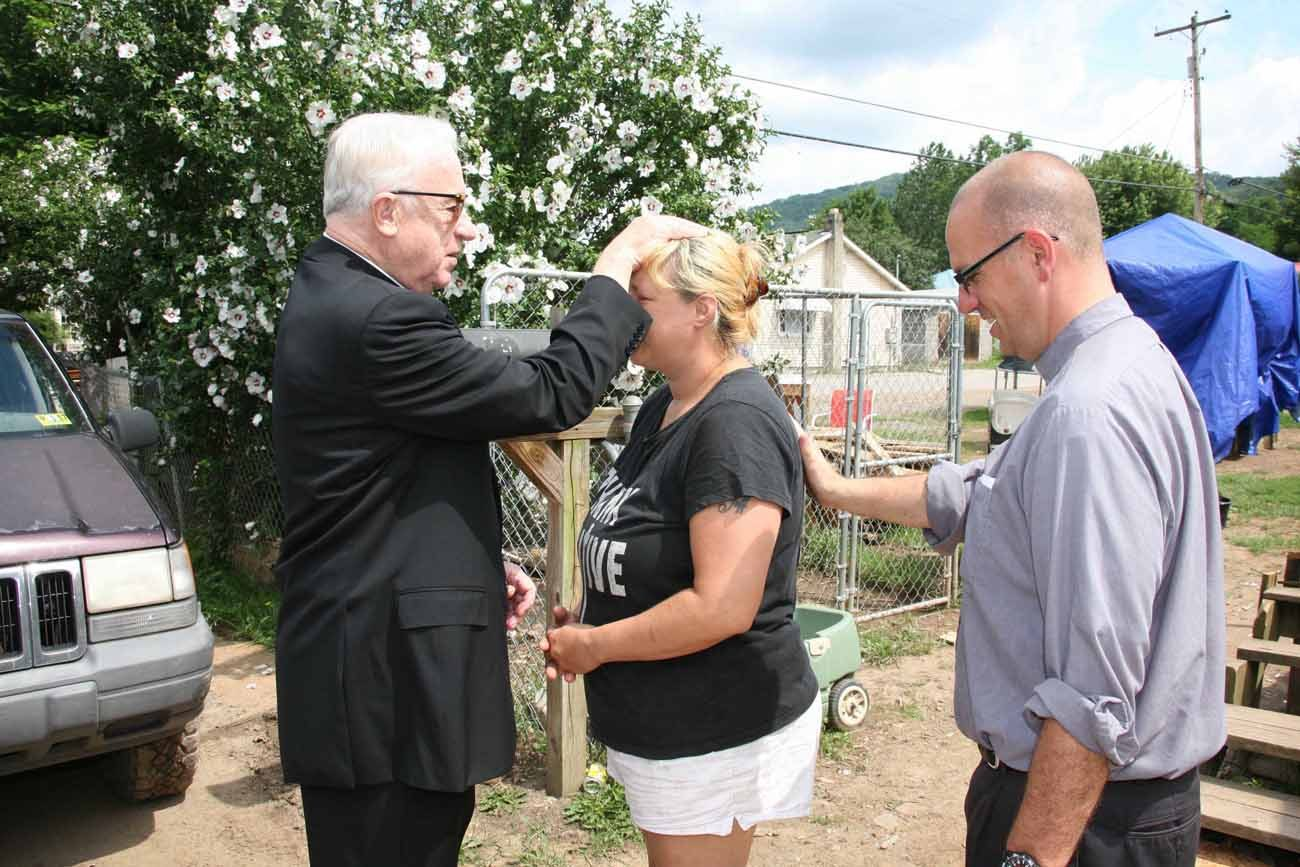 Bishop Michael J. Bransfield of Wheeling-Charleston, W.Va, bestows a blessing July 19 on Nancy Mullins of Richwood, W.Va., whose house was destroyed in the June 23 flood. With them is Deacon David Galvin of St. James Parish in Charles Town, W.Va., who has been volunteering in recovery efforts. (CNS photo/Colleen Rowan)
