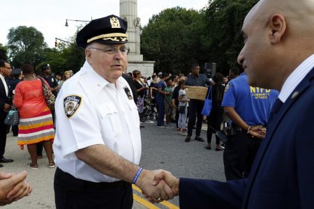 Msgr. Robert Romano, a New York City police chaplain, greets a man before the start of a candlelight vigil July 11 at Grand Army Plaza in the Prospect Heights section of Brooklyn, N.Y. (CNS photo/Gregory A. Shemitz)