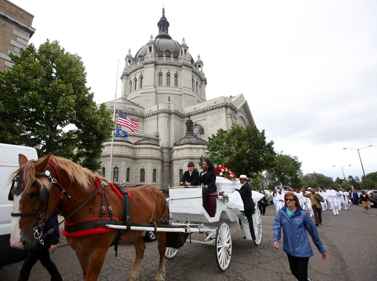 A horse-drawn carriage carries the casket of Philando Castile July 14 as it passes the Cathedral of St. Paul in St. Paul, Minn. Church officials say the mother of 32-year-old man, who was not Catholic, requested the cathedral hold an ecumenical funeral service for her son. Castile was shot and killed by a police officer July 6. (CNS photo/Dave Hrbacek, The Catholic Spirit)