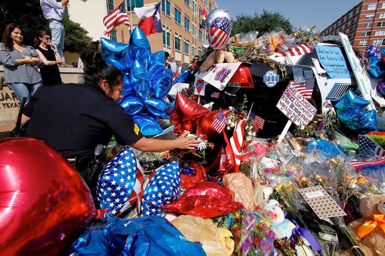 Sgt. Rocio Munoz of the Dallas Police Department inspects a memorial to slain officers outside department headquarters in Dallas July 11. (CNS photo/Kevin Bartram)