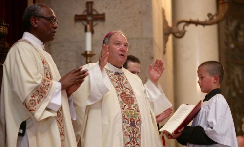 Deacon Phil Stewart looks on as Archbishop Bernard A. Hebda of St. Paul and Minneapolis reads a prayer during a July 8 Mass for peace and justice at the Cathedral of St. Paul. (CNS photo/Dave Hrbacek, The Catholic Spirit)