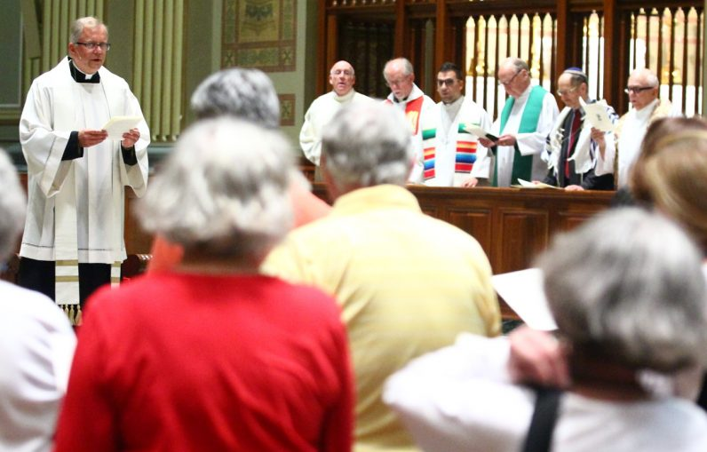 Clergy from Christian and Jewish congregations in the Philadelphia area, led by Father G. Dennis Gill (left) of the Cathedral Basilica of SS. Peter and Paul, pray during the interfaith service at the cathedral July 25 during the Democratic National Convention in Philadelphia. (Sarah Webb)