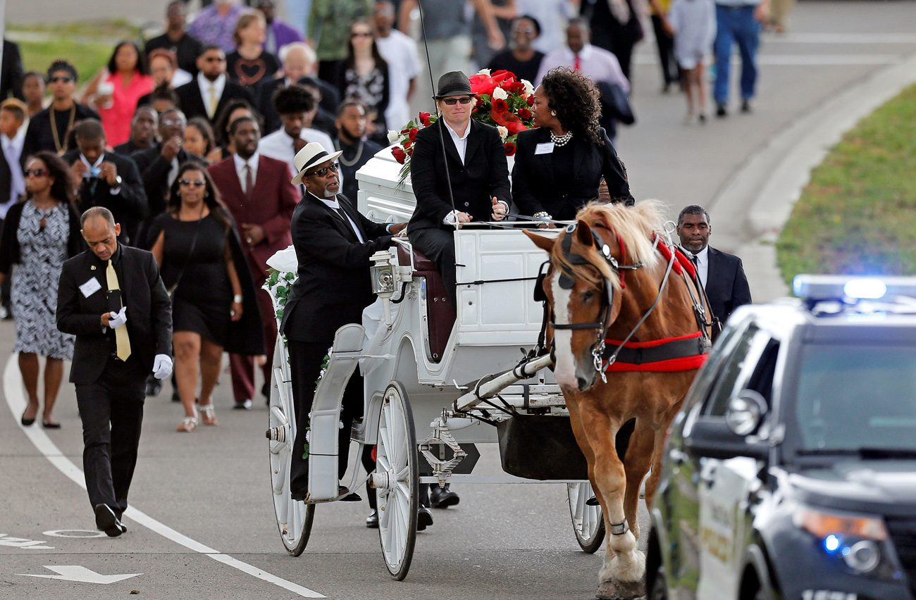 A horse-drawn carriage carries the casket of  Philando Castile July 14 during a procession to the Cathedral of St. Paul in St. Paul, Minn. Church officials say the mother of 32-year-old man, who was not Catholic, requested the cathedral hold an ecumenical funeral service for her son. Castile was shot and killed by a police officer July 6. (CNS photo/Eric Miller, Reuters)