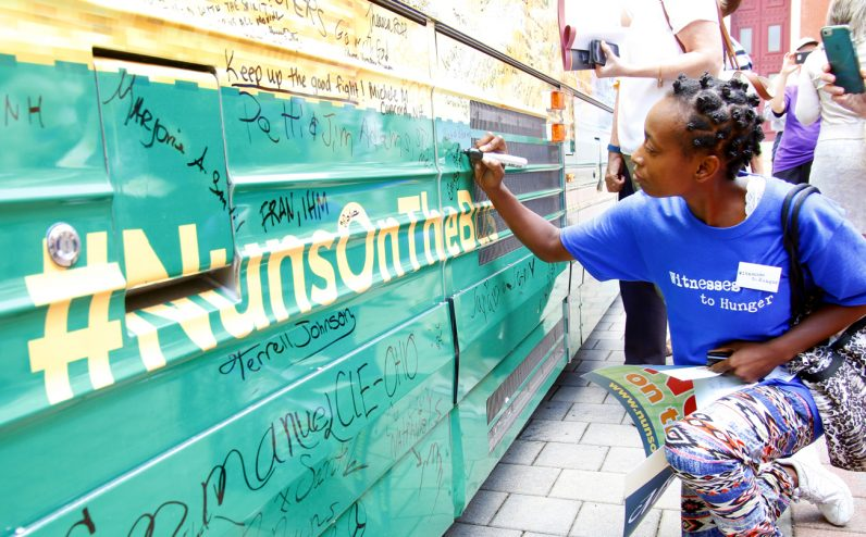Emily Edwards of Witnesses to Hunger signs the  sisters' bus after giving her testimony at the closing rally in Philadelphia.