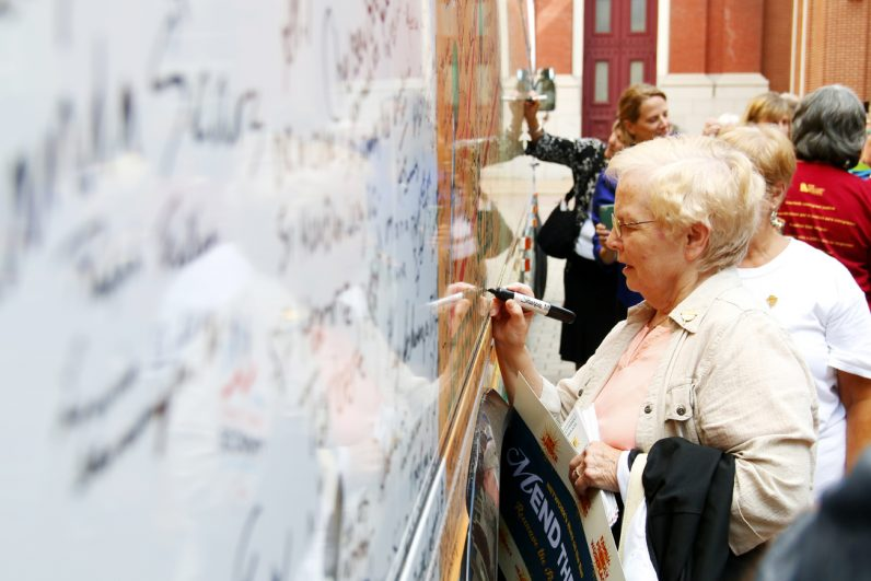 Sister Mary Elizabeth Farrell, S.S.J., signs the bus to show her support for the sisters' social justice efforts after attending the closing rally of their road trip.
