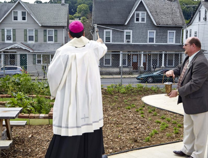 Bishop John McIntyre blesses the victory garden and the Operating Base Cecilia and its grand opening in Coatesville June 30, as Ed Lis, an official with Catholic Social Services, assists. The CSS-run facility helps up to 75 former military servicemen and their families each month in the converted former Catholic school.