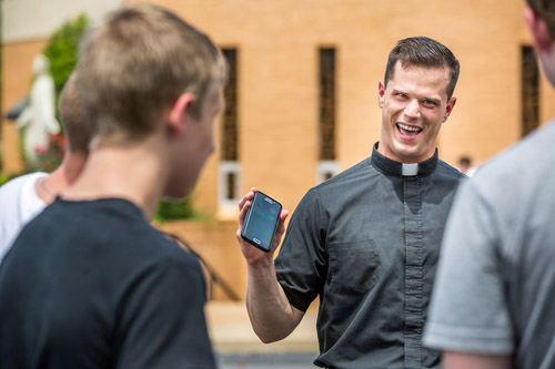 Father David Miloscia of Assumption Parish in St. Louis shows young people the game Pokemon Go on his cellphone as they chase Pokemon stops around the church grounds July 14. (CNS photo/Lisa Johnston, St. Louis Review)