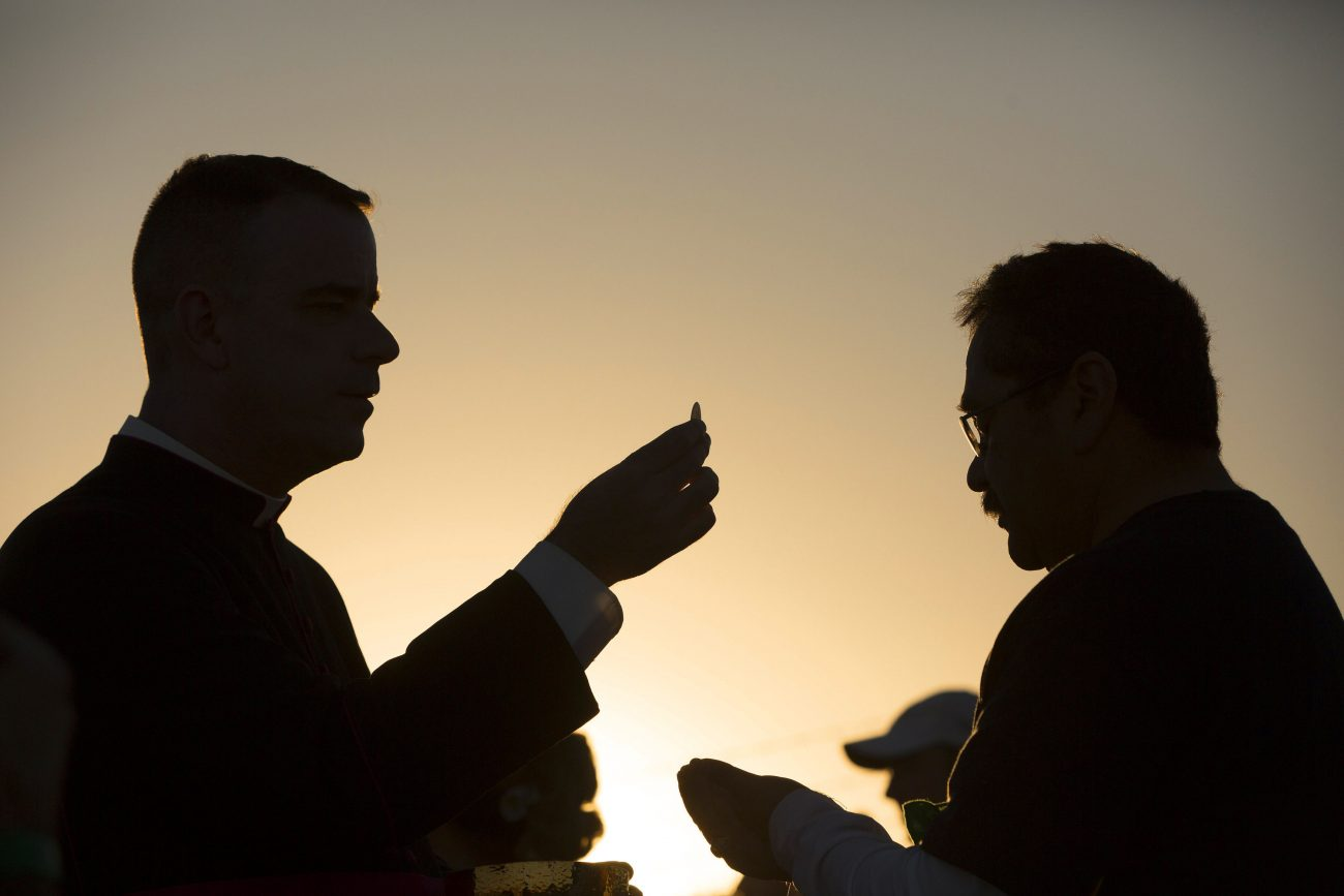Msgr. J. Brian Bransfield, a Philadelphia priest and general secretary of the United States Conference of Catholic Bishops, gives Communion to a man attending Mass on the U.S. side of the border in El Paso, Texas in this February 2016 file photo. (CNS photo/Nancy Wiechec)