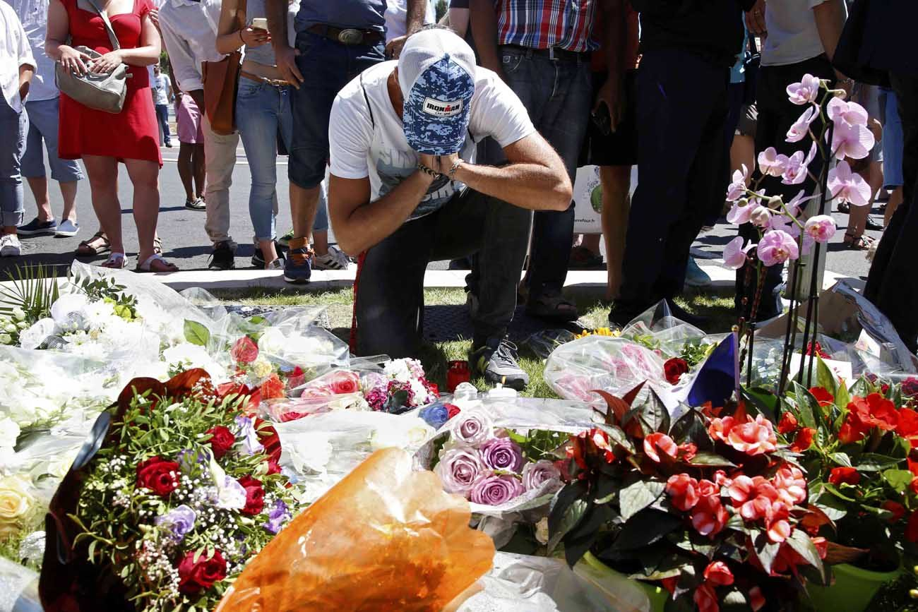 A man prays in front of a makeshift memorial July 15 in Nice, France, as people pay tribute near the scene where a truck ran into a crowd killing more than 80 people the previous evening. (CNS photo/Pascal Rossignol, Reuters)