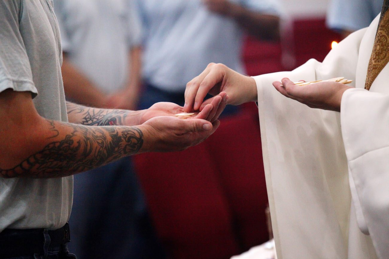 Father Joshua Werth distributes Communion to an inmate during a June 9 Mass at the Ellsworth Correctional Facility in Kansas. (CNS photo/Karen Bonar, The Register)