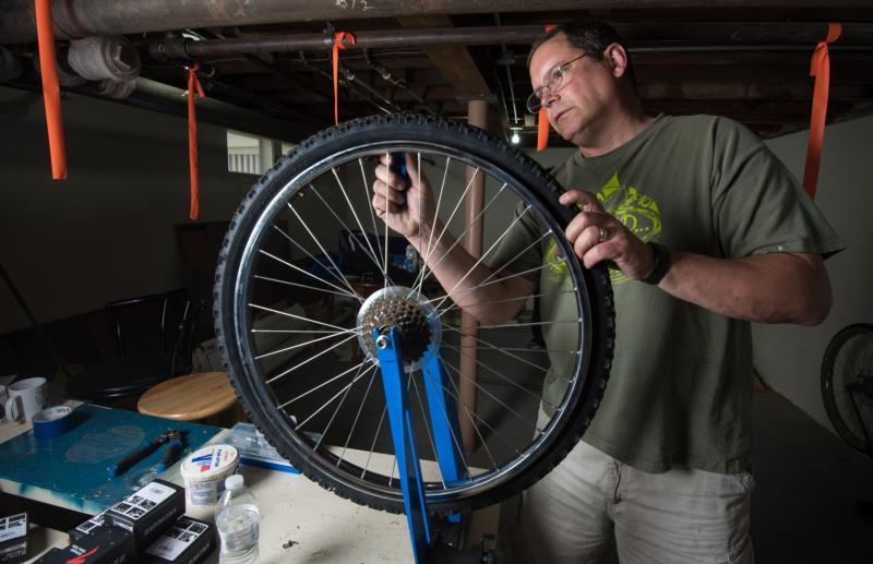 Tony Pichler, a member of the St. John the Evangelist Homeless Shelter's ministry team in Green Bay, Wis., repairs the inner tube on a bicycle tire June 7. Pichler and Paula Rieder, coordinator of pastoral ministry at St. Raphael the Archangel Parish in Oshkosh, Wis., were instrumental in launching Spokes 4 Hope. (CNS photo/Sam Lucero, The Compass)