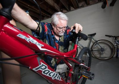 Tom Mayhew tests the brakes on a bicycle in the basement of St. John the Evangelist Church rectory in Green Bay, Wis. Mayhew, a retired dentist, was homeless and turned to the shelter after his practice went bankrupt. Now back on his feet, he says repairing bikes is a way for him to give back to the shelter. (CNS photo/Sam Lucero, The Compass) See SHELTER-WHEELS-HOPE July 6, 2016.