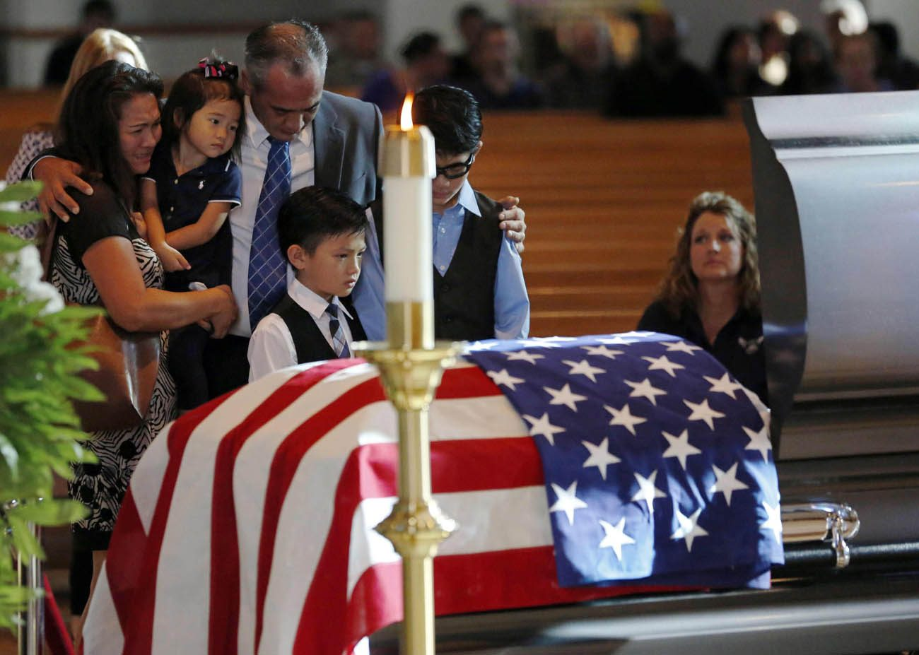 Billy Smith, brother of slain Dallas Police Sgt. Michael Smith, and his family grieve at the officer's casket during a July 12 visitation for him at Mary Immaculate Catholic Church in Farmers Branch, Texas. Smith, a member of the parish, was one of five officers killed when a gunman opened fire at a July 7 protest in downtown Dallas. (CNS photo/G.J. McCarthy, The Dallas Morning News pool via Reuters)