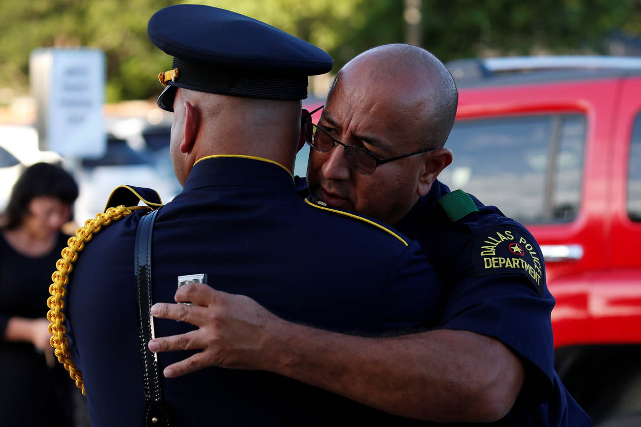 Police officers hug outside Mary Immaculate Catholic Church in Farmers Branch, Texas, during the July 12 visitation for slain Dallas police Sgt. Michael Smith. Smith, a member of the parish, was one of five officers killed when a gunman opened fire at a July 7 protest in downtown Dallas. (CNS photo/Carlo Allegri, Reuters)
