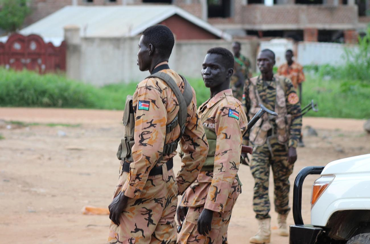 South Sudanese policemen and soldiers stand guard along a street following renewed fighting July 10 in Juba. South Sudan's church leaders said they are extremely disturbed about heavy fighting in the capital, which has raised widespread fears that the country is returning to civil war. (CNS photo/Reuters)