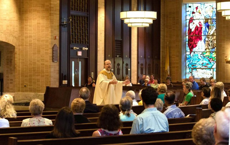 Father John Hallinan, pastor of St. John Chrysostom Parish in Wallingford, preaches the homily during the Community Mass for Peace celebrated July 20 at the parish church. (Ed Quinn)