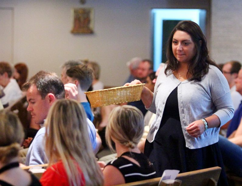 Angelica Corridini offers service to the congregation as do many young people at the Sunday evening Mass at St. Isaac Jogues in Wayne.