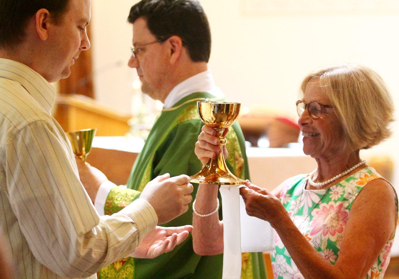 Suzette Moyer, an extraordinary minister of holy Communion, offers the Blood of Christ during during Mass July 16 at St. Mary Church, Schewnksville. Permanent Deacon Donald O. Nichols also distributes Communion. A new Vatican commission will look at the ministerial role of women in the early Christian church, with possible implications for  roles in the church today. (Photo by Sarah Webb)