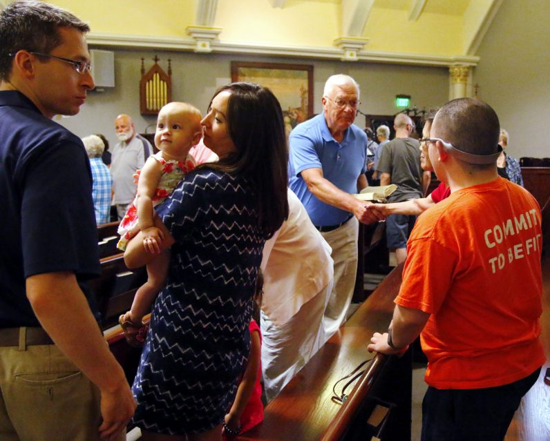 People exchange a sign of peace at the Saturday evening Mass July 16 at St. Teresa of Calcutta Parish, which is celebrating its 10th anniversary in Limerick.