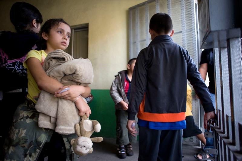 A young girl holds her belongings as she waits with a group of Mexicans preparing to leave the Casa del Migrante shelter  June 8 in Tijuana, Mexico. (CNS photo/David Maung)