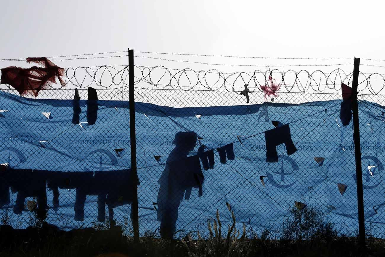 A refugee woman hangs her laundry behind a fence at a transit camp in Schisto, Greece, April 4. (CNS photo/Yannis Kolesidis, EPA).