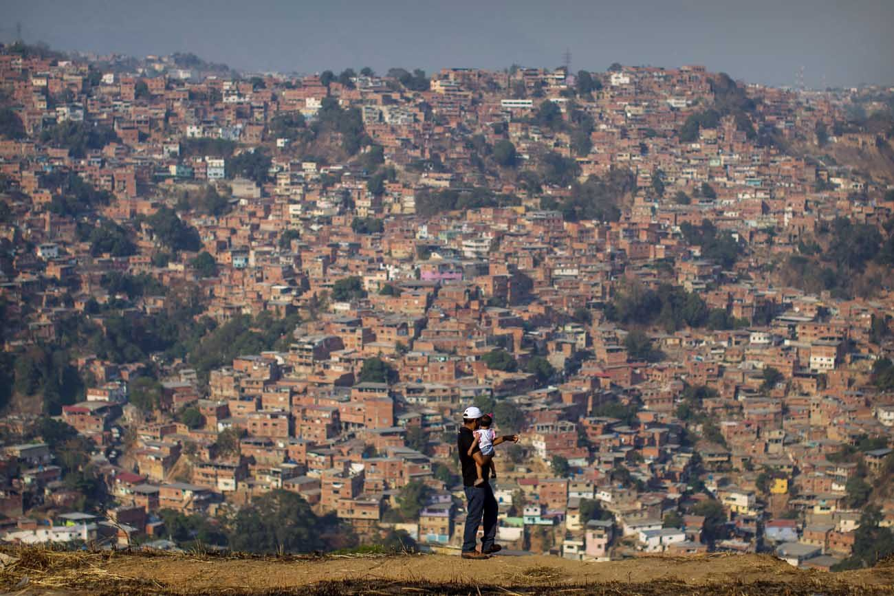 A man and his daughter overlook a neighborhood in Caracas, Venezuela, March 25. Venezuela's deepening economic crisis  has prompted Catholics to turn to the church, which does not have enough donations to help everyone. (CNS photo/Miguel Gutierrez, EPA)