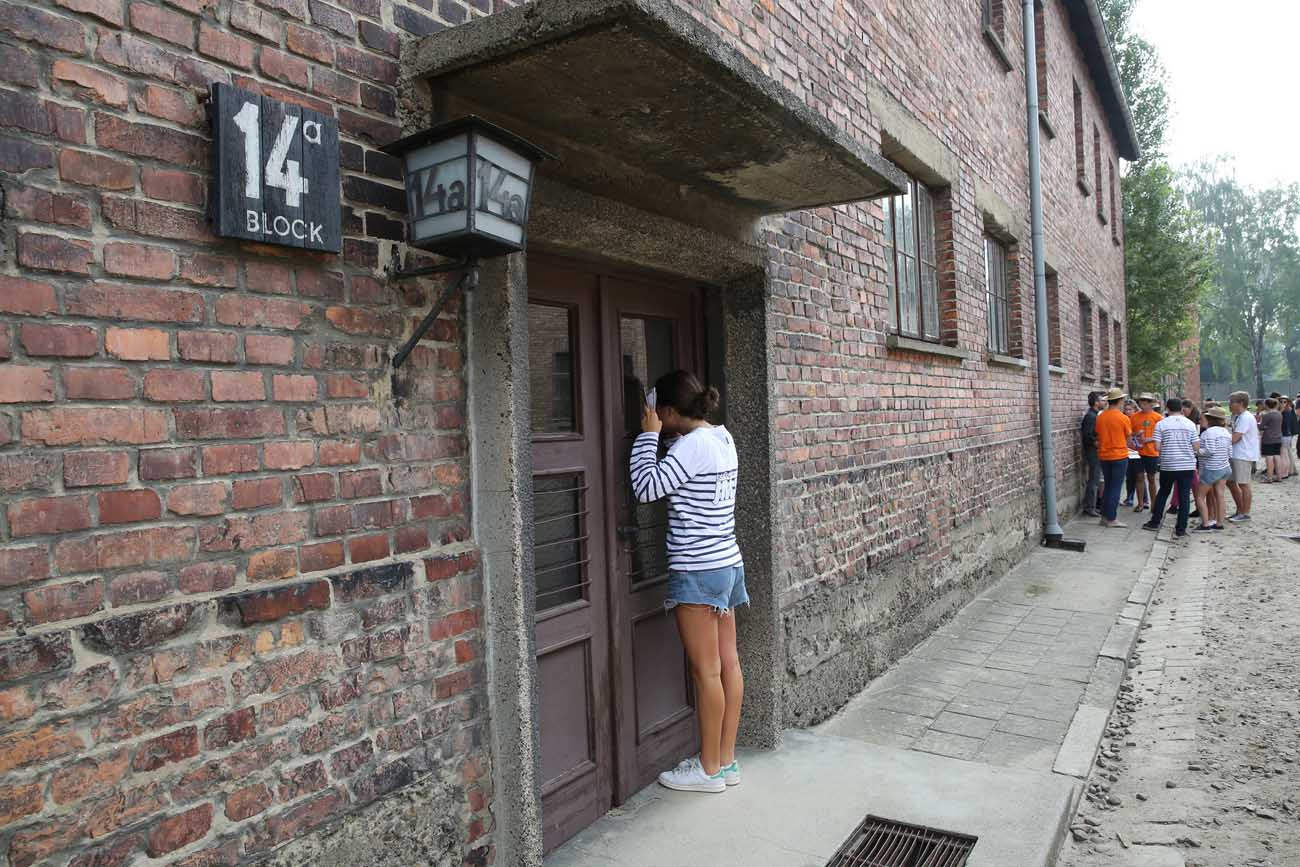 A World Youth Day pilgrim looks inside a building during a July 25 visit to the Auschwitz Nazi concentration camp in Oswiecim, Poland. (CNS photo/Bob Roller)