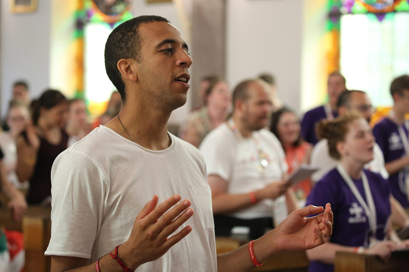 Sean Goug, 26, of England, prays at Sacred  Heart Church in Krakow, Poland, July 28. (CNS photo/Bob Roller)