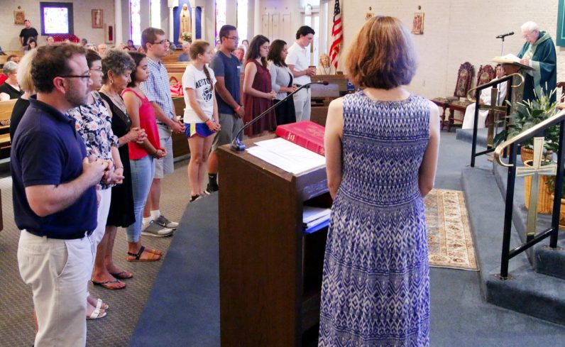 Father Edward Hamilton offers a special blessing for those who will depart July 21 for World Youth Day.