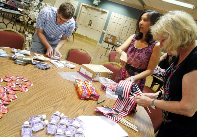 Young people and parents pack trinket bags they will take to World Youth Day to exchange with other youths.