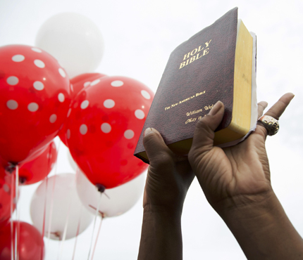 A resident holds up a Bible during a July 7 vigil in memory of Alton Sterling, who was shot dead by police outside a market in Baton Rouge, La. (CNS photo/Jeffrey Dubinsky, Reuters)