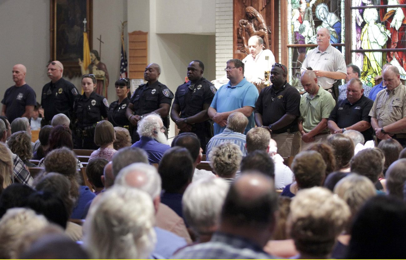 Police officers attend a July 17 vigil at St. John the Baptist Church in Zachary, La., for the fatal attack on policemen in Baton Rouge, La. Archbishop Wilton D. Gregory of Atlanta has been appointed as chair of a task force of U.S. bishops to help them address racial issues following a series of summertime shootings that left both citizens and police officers among the dead. (CNS photo/Jeffrey Dubinsky, Reuters)