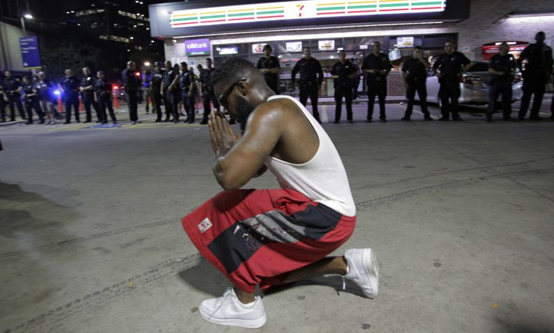 A protester prays near Dallas police officers July 7 after police officers were shot during a protest in Dallas.  (CNS photo/Ralph Lauer, EPA)