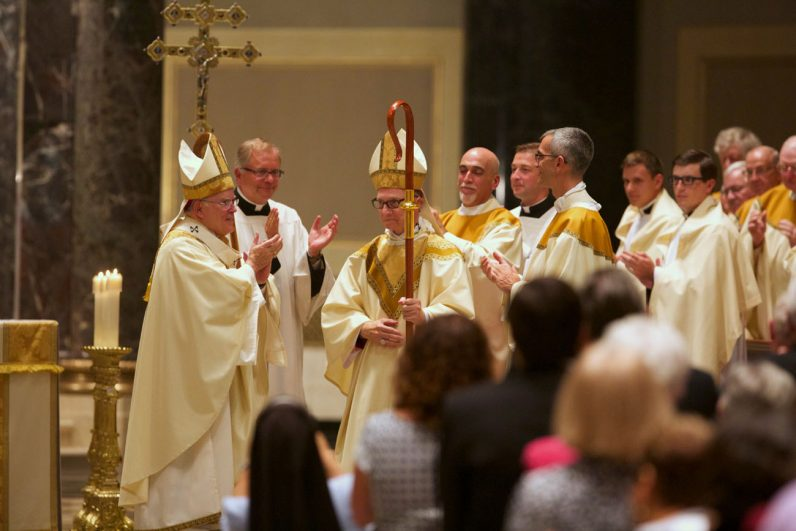 Everyone in the capacity congregation in the cathedral stands to applaud their new auxiliary bishop. (Bradley Digital)