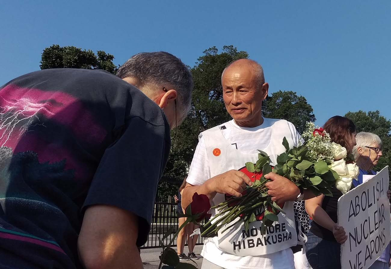 Hiroshima survivor Toshiyuki Mimaki receives roses from a peace activist  in front of the White House in Washington Aug. 6, the 71st anniversary of the U.S. dropping an atomic bomb on Hiroshima, Japan. (CNS photo/James Martone)