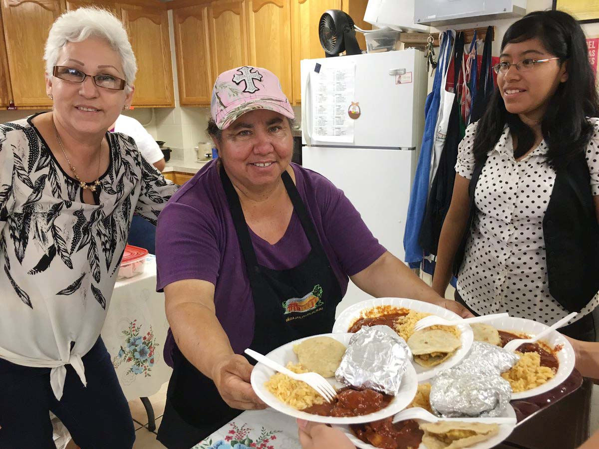 Carmen Alvear and other parishioners from San Felipe de Jesus Parish in Brownsville, Texas, prepare a special meal for unaccompanied children from Central America who attend Mass at their church July 10. (CNS photo/Rose Ybarra, The Valley Catholic)
