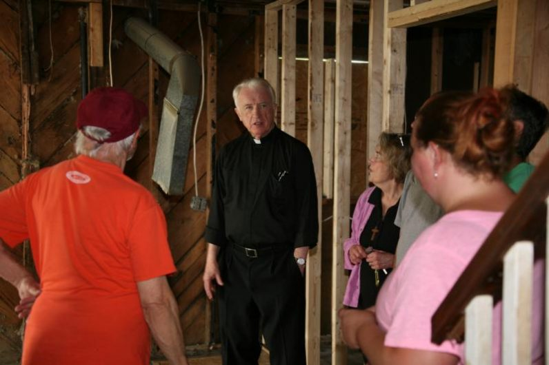 Bishop Michael J. Bransfield of Wheeling-Charleston, W.Va., tours a home in Rainelle, W.Va., July 25 that was damaged by flood waters in June. (CNS photo/Tim Bishop, Catholic Spirit)
