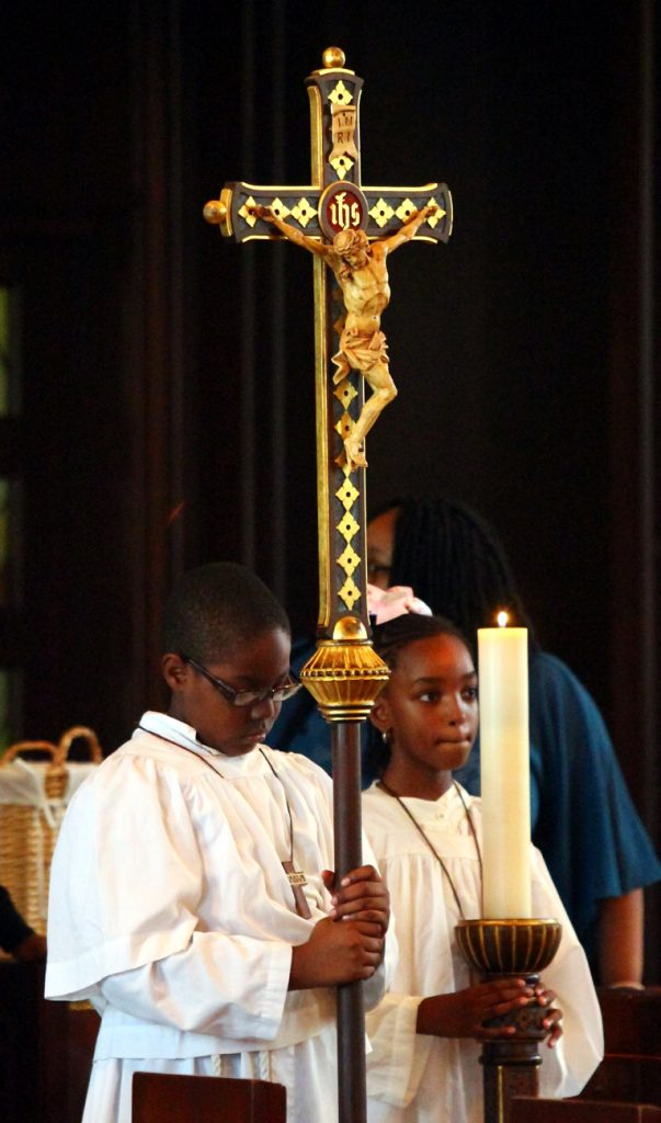 Altar servers Hedwig Dorismond and Marvanley Niosette process to begin Mass.