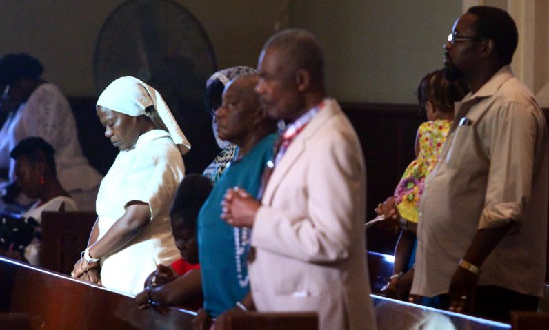 Sister Dona Belizoire, S.R.N., prays with other worshipers in Haitian Creole during the Mass at St. William Church.