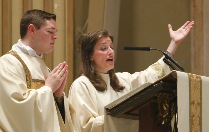 Cathedral cantor Charlene Angelini leads the congregation in song, with Deacon Matthew Brody nearby. (Sarah Webb)