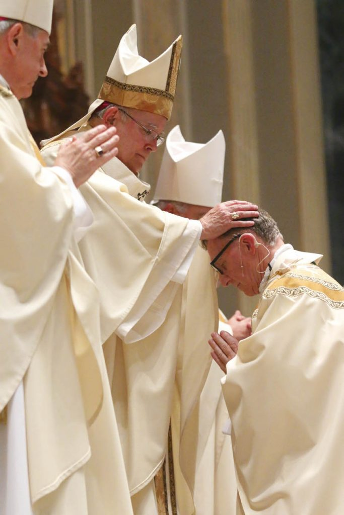Archbishop Charles Chaput lays hands on Bishop Edward Deliman during the ordination rite. (Sarah Webb)