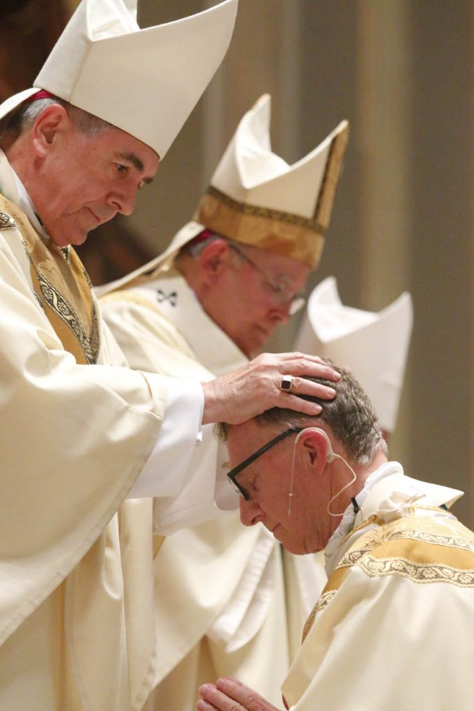 Bishop Ronald Gainer of the Diocese of Harrisburg, also a co-consecrator, lays his hands on Bishop Deliman. The two studied in the same class at St. Charles Borromeo Seminary and were ordained the same year, 1973. (Sarah Webb)